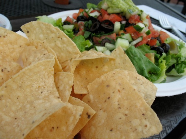 Salad piled high with veggies and guac and a basket of chips on the side.