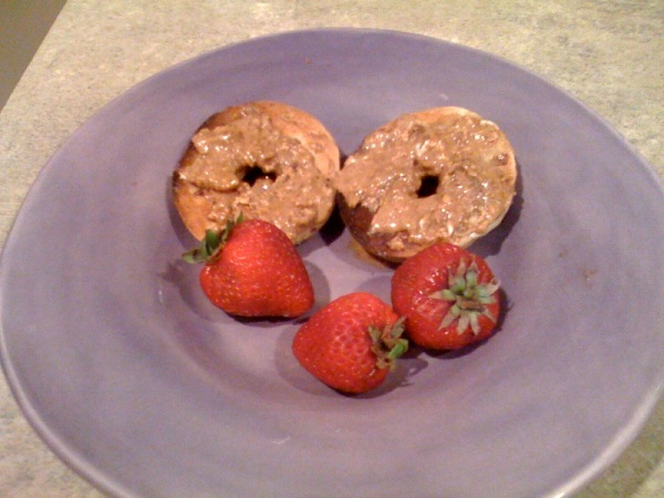 Toasted bagel with almond butter and strawberries.
