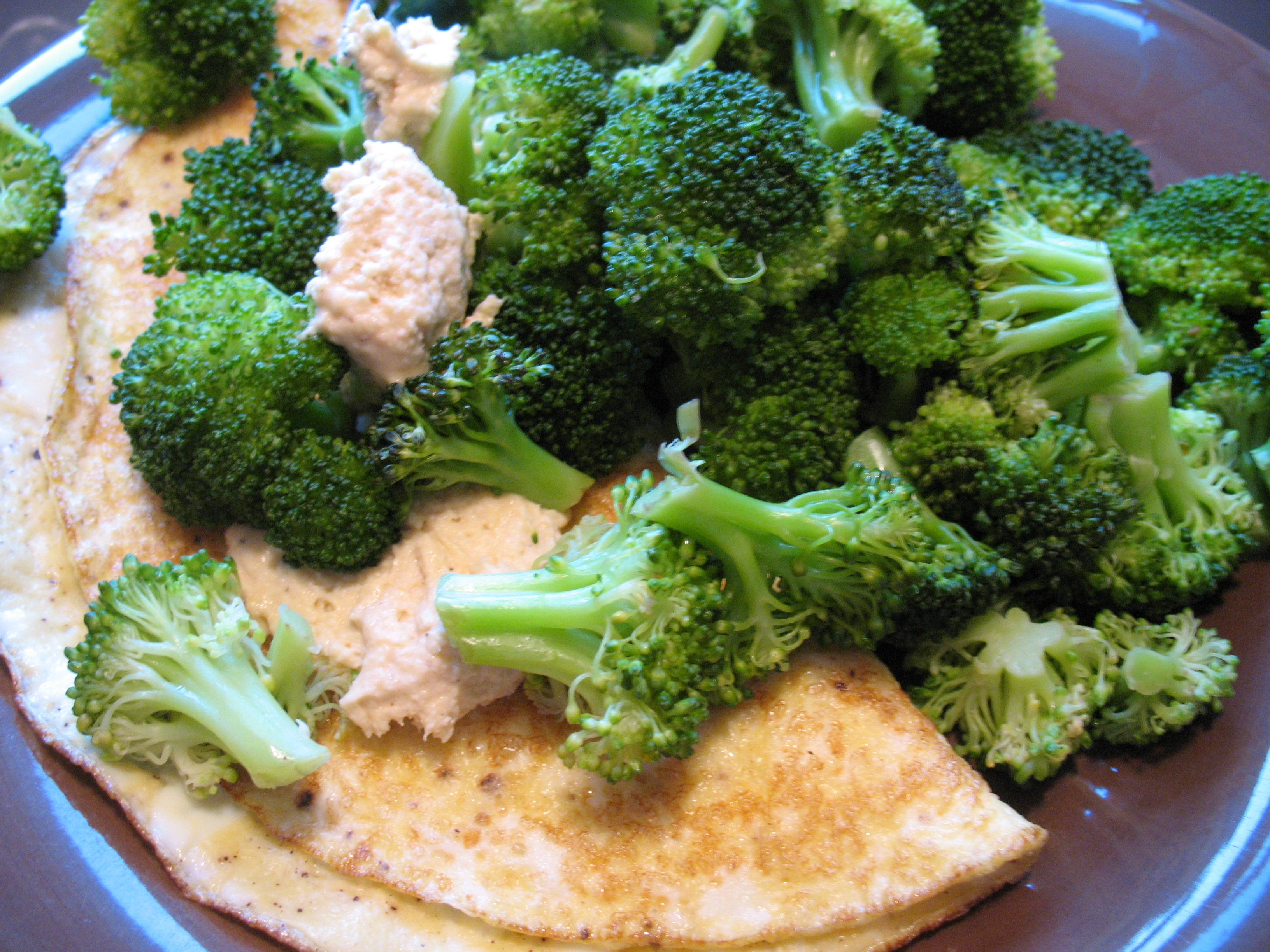 An omelet (1 whole egg + 3 whites) with steamed broccoli and hummus.