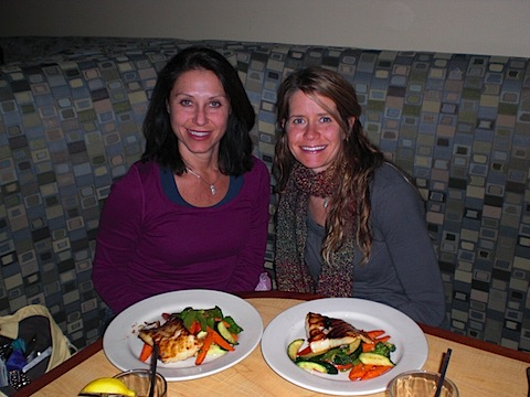Heather & Deb sitting in booth with plates of food in front of them